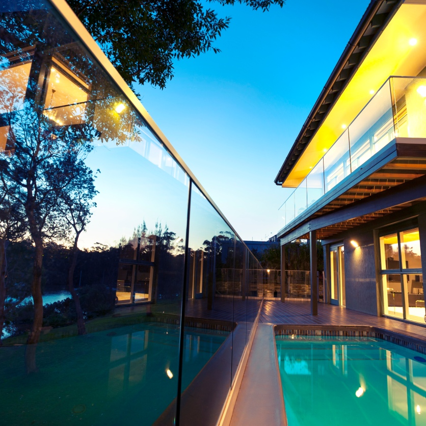 Waterfront house with swimming pool at sunset