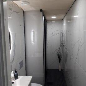 Satiinilasiseinä mustilla listoilla ja heloilla jakaa kodinoitohuoneen WCstä JVG Laseja Oy